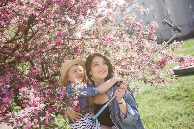 Jonge mooie moeder en haar dochtertje selfie maken op mobiele telefoon.