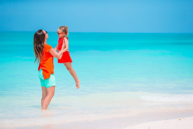 Jonge mooie moeder en haar schattige dochtertje hebben plezier op tropisch strand