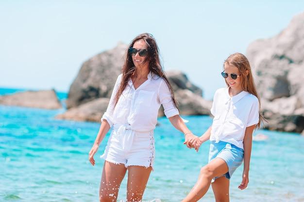 Jonge mooie moeder en haar schattige dochtertje plezier op het strand