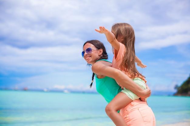 Jonge mooie moeder en haar schattige kleine dochter flyinf als een vogel op tropisch strand