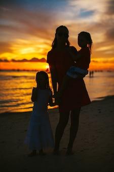 Jonge mooie moeder en haar schattige kleine dochters op het strand bij zonsondergang