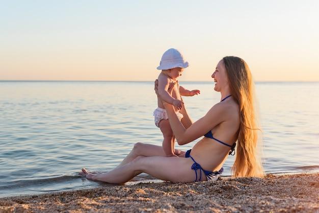 Jonge mooie moeder en kind aan zandstrand tegen de zee en de zonsondergang. familie vakantie