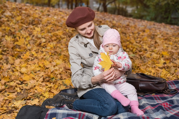 Jonge mooie moeder en kind in de herfst park op geel