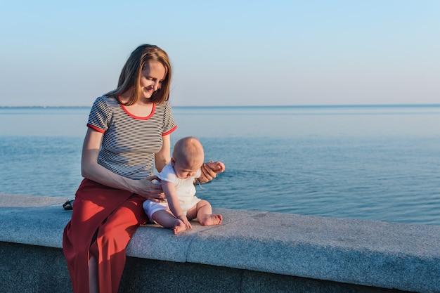 Jonge mooie moeder en kleine baby op promenade op zee