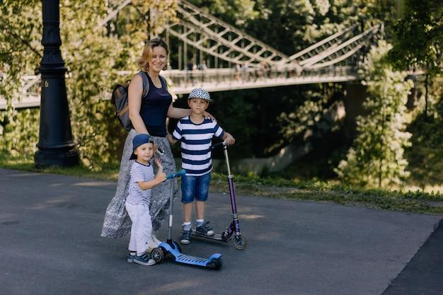 Jonge mooie moeder geniet van wandelen in het park met twee zonen op scooters