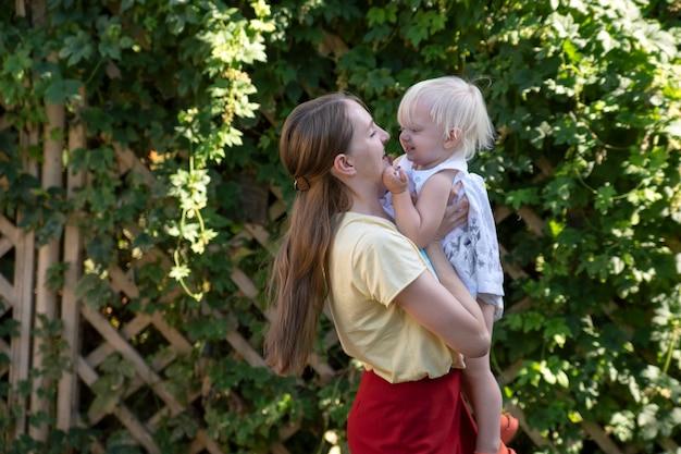 Jonge mooie moeder houdt kind in haar armen. portret van moeder en peuter buitenshuis.