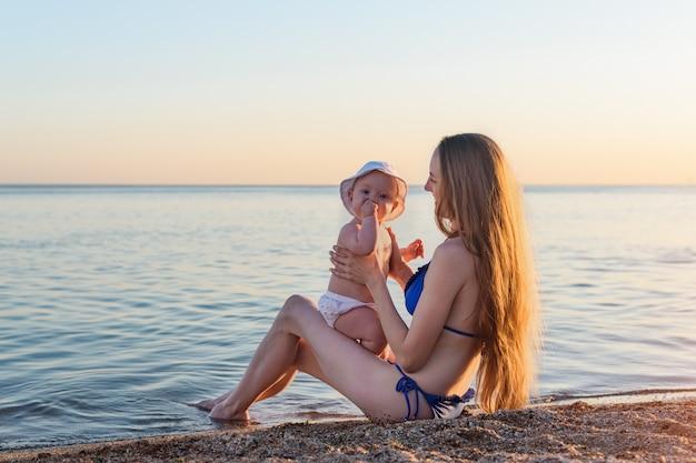 Jonge mooie moeder in zwembroek met de baby op strand. moeder en baby op zee