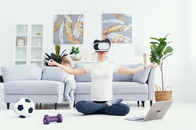 Jonge mooie moeder mediteren in yoga lotuspositie met behulp van virtual reality-bril terwijl haar dochter tekenfilms thuis op de achtergrond bekijkt.