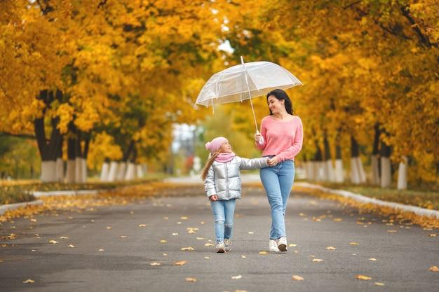 Jonge mooie moeder met haar dochtertje plezier. in de herfst en gelukkige familie