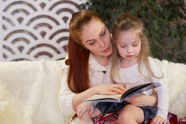 Jonge mooie moeder met haar kleine dochter die een boekzitting op de laag leest.