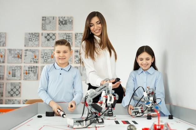 Jonge mooie moeder met haar zoon en dochter poseren op de school voor robotica met robots van de constructeur.