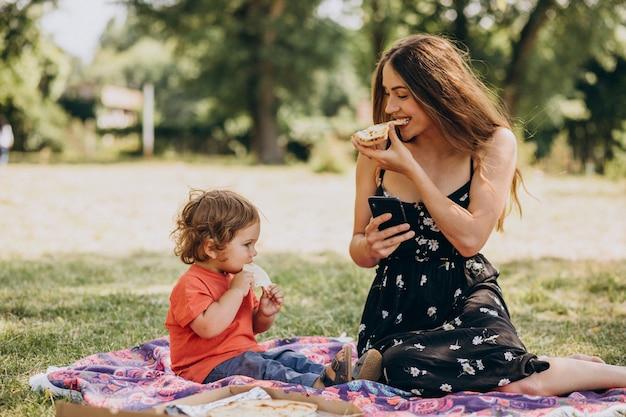Jonge mooie moeder met kleine babyjongen eet pizza in park