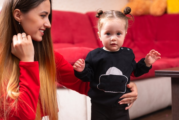 Jonge mooie moeder met lang haar met haar schattige kleine babymeisje dat leert lopen