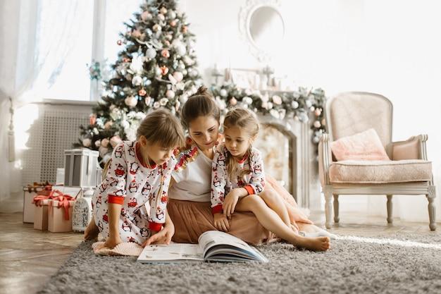 Jonge mooie moeder met twee kleine dochters zitten op het tapijt en lees een boek in de buurt van de nieuwjaarsboom met geschenken in de lichte, gezellige kamer met fauteuil en open haard. .