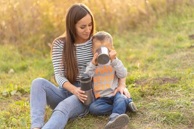 Jonge mooie moeder met zoontje geniet van de natuur