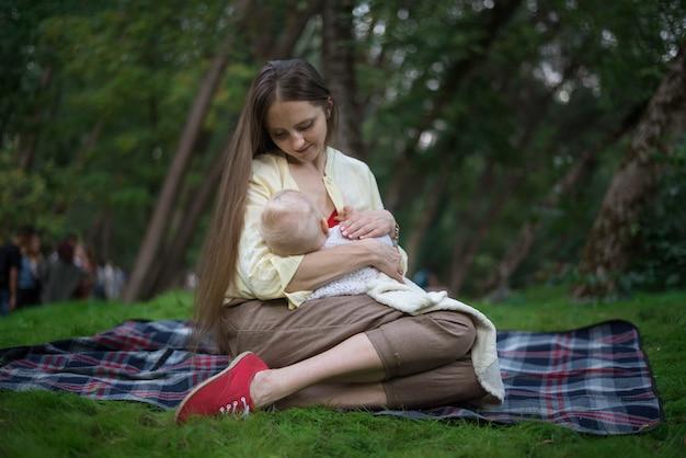 Jonge mooie moeder pasgeboren knuffelen en de borst geeft. picknick met baby in park