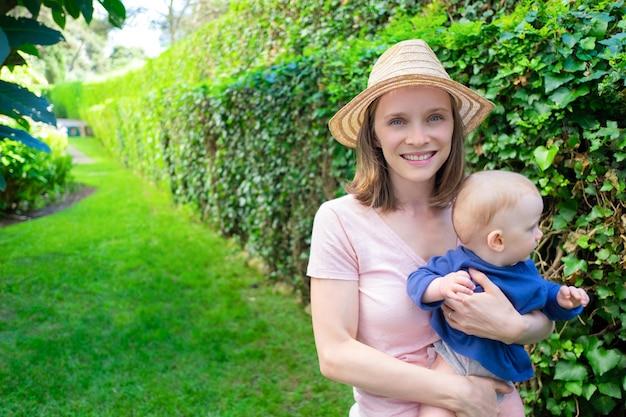 Jonge mooie moeder permanent in park, dochter te houden, glimlachend en camera kijken. aanbiddelijk babymeisje dat groene struik bekijkt. familie zomertijd, tuin