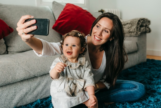 Jonge mooie moeder speelt met haar dochter die selfies neemt