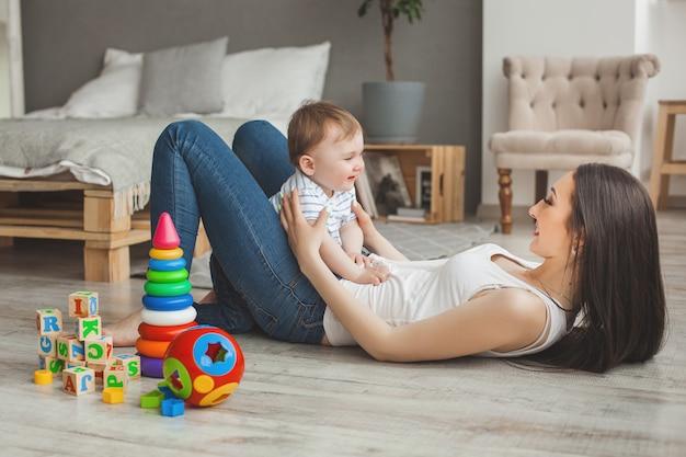 Jonge mooie moeder speelt met haar zoontje. vrolijke familie plezier binnenshuis met kleine baby zoon