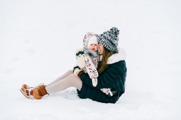 Jonge mooie moeder spelen met dochtertje buiten in de winter.