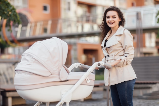 Jonge mooie moeder wandelen met kinderwagen in het centrum van de europese stad.
