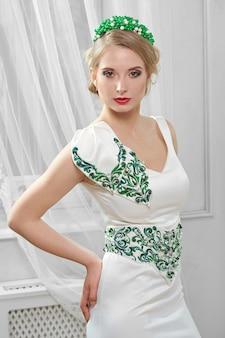 Jonge mooie, mooie vrouw in lichtroze korte jurk met rood