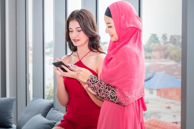 Jonge mooie moslimvrouw en kaukasische vriendschappen met telefoon en creaditkaart die in het winkelen bij woonkamer genieten van