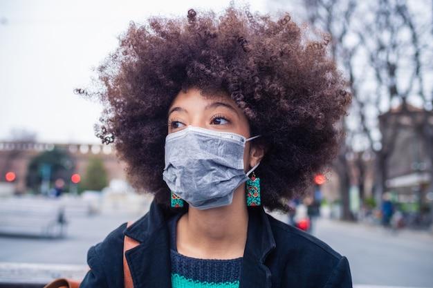 Jonge mooie multi-etnische vrouw die medisch masker draagt dat tegen verontreiniging en virus beschermt