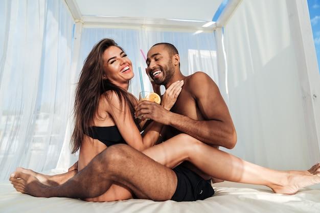 Jonge mooie multiraciale verliefde paar met plezier op het strand