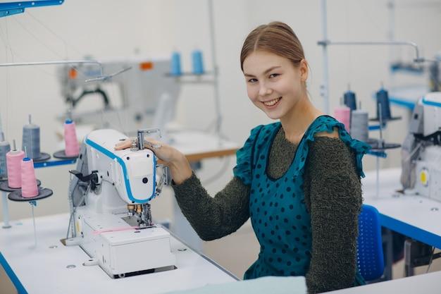 Jonge mooie naaister naait op naaimachine in fabriek.