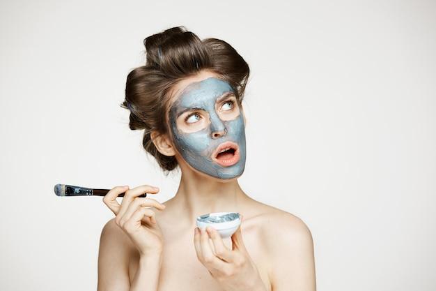 Jonge mooie naakte vrouw in haarkrulspelden die gezicht behandelen met mack. geopende mond. gezichtsbehandeling. schoonheid cosmetologie en spa.
