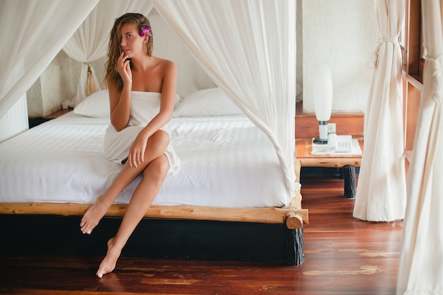 Jonge mooie natuurlijke sexy vrouw na douche, badhanddoek, zittend op bed, witte lakens, tropisch hotel, honingmaan, bloem orchidee, glimlachen, romantisch, verlegen, slank gebruind lichaam, nat haar, toevlucht, flirterig