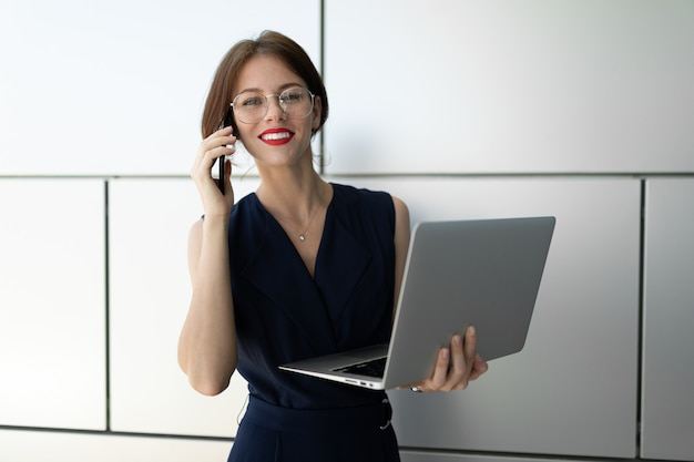 Jonge mooie office vrouw met lichte make-up, rode lippen, bril zit, communiceert met iemand of werkt met laptop
