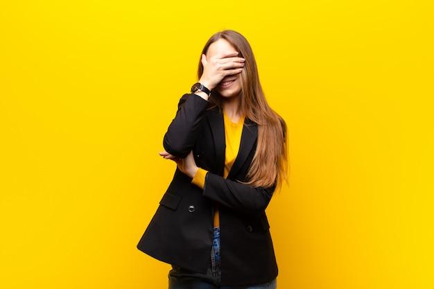 Jonge mooie onderneemster die beklemtoond, beschaamd of overstuur, met een hoofdpijn, die gezicht behandelt met hand tegen sinaasappel