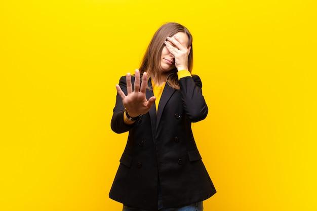Jonge mooie onderneemster die gezicht behandelt met hand en andere hand vooraan zet om camera tegen te houden, die foto's of beelden weigert
