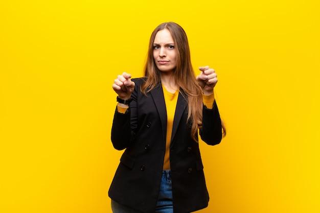 Jonge mooie onderneemster die vooruit op camera met zowel vingers als boze uitdrukking richt, die u vertelt om uw plicht op sinaasappel te doen