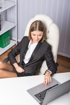 Jonge mooie onderneemster met laptop in bureau.