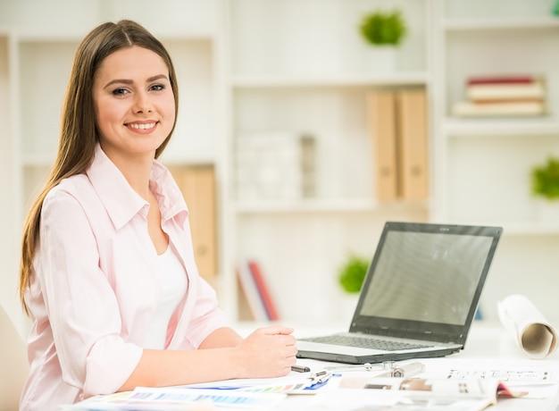 Jonge mooie ontwerper die laptop in haar bureau met behulp van.