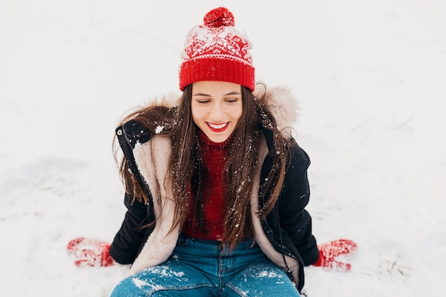 Jonge mooie openhartige lachende gelukkige vrouw in rode wanten en gebreide muts dragen zwarte jas wandelen spelen in park in de sneeuw, warme kleren, plezier
