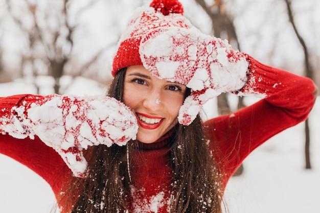 Jonge mooie openhartige lachende gelukkige vrouw in rode wanten en muts dragen gebreide trui wandelen spelen in park in de sneeuw, warme kleren, plezier