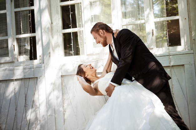 Jonge mooie opgedirkte jonggehuwden glimlachen, buitenshuis dansen.