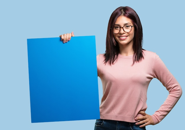 Jonge mooie opgewekte en gemotiveerde vrouw, die een lege affiche toont waar u een bericht, communicatie concept kunt tonen