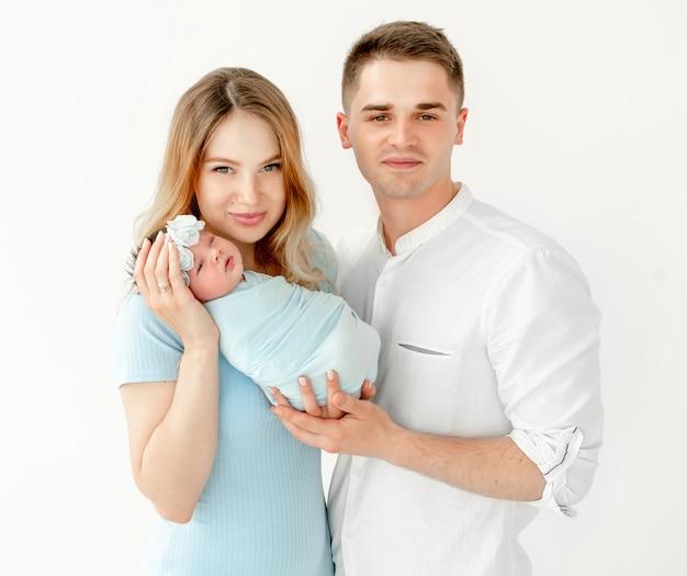 Jonge mooie ouders die een pasgeboren dochter houden