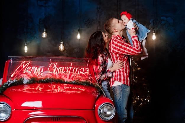 Jonge mooie ouders houden hun kleine schattige dochter in hun armen met plezier in de buurt van retro auto in de studio. kerst familie look. nieuwjaars landschap.