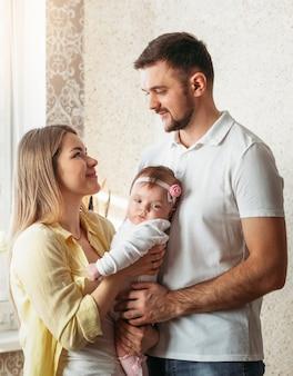 Jonge mooie ouders man en vrouw met baby dochter in armen kijken elkaar aan