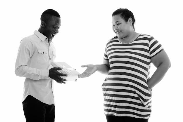 Jonge mooie overgewicht aziatische vrouw en jonge afrikaanse man samen als paar in zwart-wit