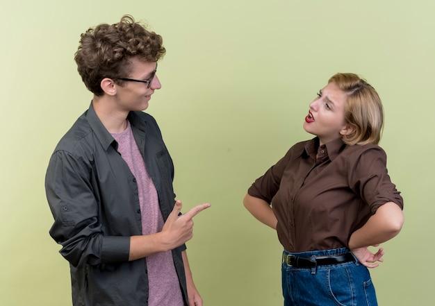 Jonge mooie paar dragen casual kleding man en vrouw ruzie staande over lichte muur