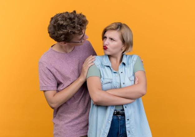 Jonge mooie paar dragen vrijetijdskleding man om vergeving vraagt ontevreden vrouw na gevecht over sinaasappel