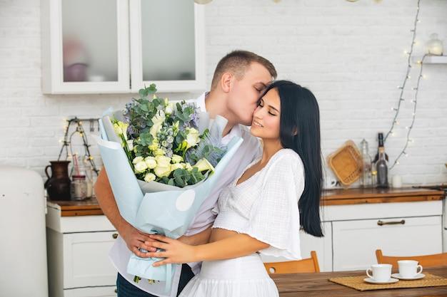 Jonge mooie paar een man geeft een vrouw bloemen voor een vakantie thuis