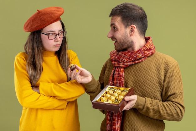 Jonge mooie paar gelukkig man chocolade snoepjes aanbieden aan zijn beledigde vriendin in baret vieren valentijnsdag staande over groene muur